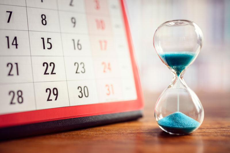A calendar sitting on a table by an hour glass filled with blue sand