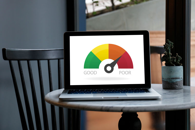 A laptop showing a fico score meter pointing to the red side.